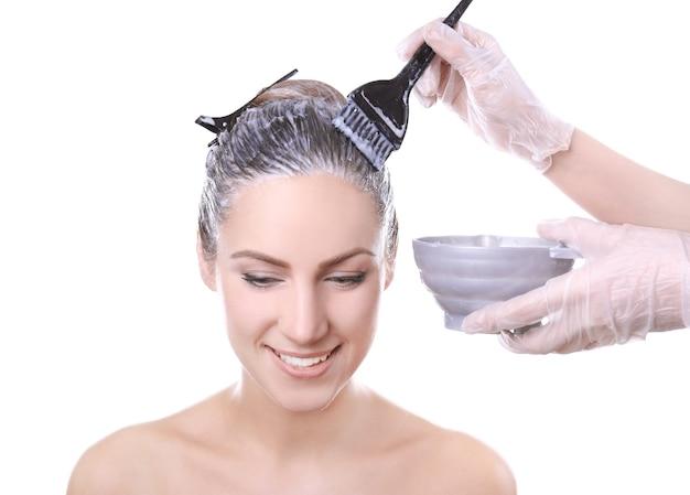 白い背景の上の若い美しい女性の髪を染める美容師
