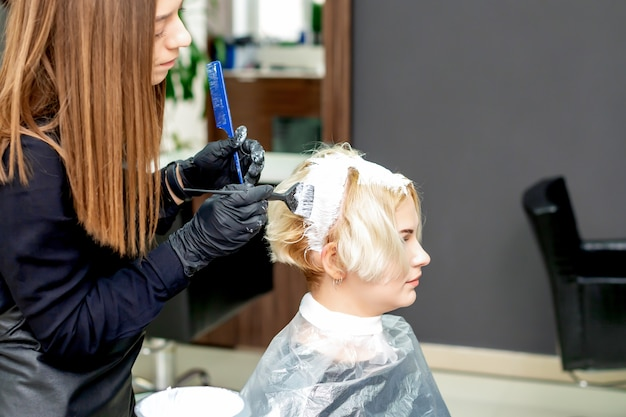 Hairdresser dyeing hair of woman in white color at beauty salon.