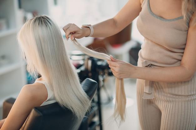 미용실에서 금발 머리를 가진 젊은 여자에게 머리 확장을 만드는 미용사 여성. 전문 헤어 익스텐션.
