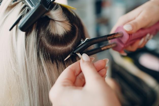미용실 전문 헤어 익스텐션에 금발 머리를 가진 젊은 여성에게 헤어 익스텐션을 만드는 미용사 여성