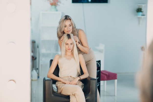 Hairdresser female making hair extensions to young woman with blonde hair in beauty salon. professional hair extension.