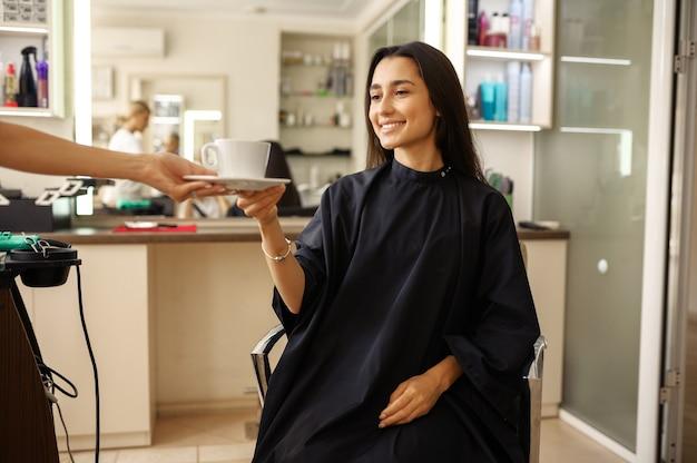 미용사는 여성 고객, 미용실에 커피 한잔을 제공합니다. 헤어 살롱의 스타일리스트와 클라이언트. 뷰티 사업, 전문 서비스