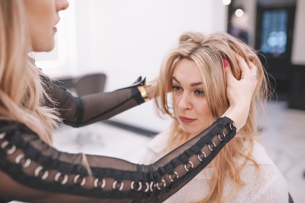 Парикмахер придает прическу молодой женщине