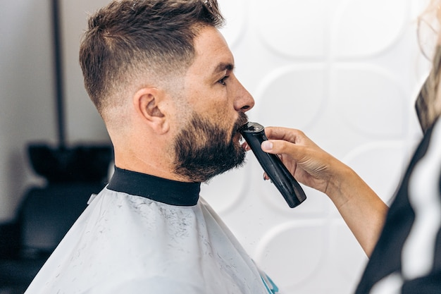 Hairdresser grooming the moustache of an adult caucasian man with an electric razor in a barber shop