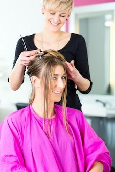 미용사-머리를 자르는 헤어 스타일리스트, 여성 고객이 이발을 얻습니다.