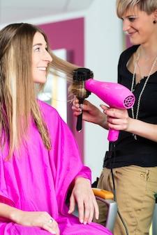 미용사-머리카락을 말리는 헤어 스타일리스트, 고객이 이발을 얻습니다.