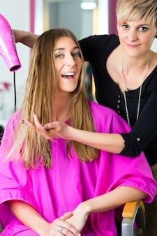 Парикмахер - парикмахер сушит волосы, клиент делает стрижку