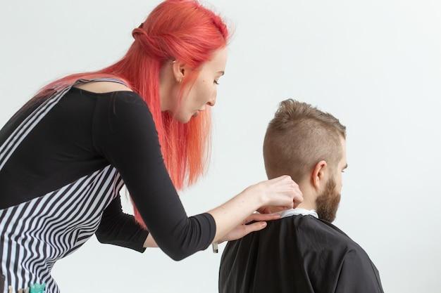 美容師、ヘアスタイリスト、理髪店のコンセプト-ひげを生やした男性をカットする女性のヘアスタイリスト。