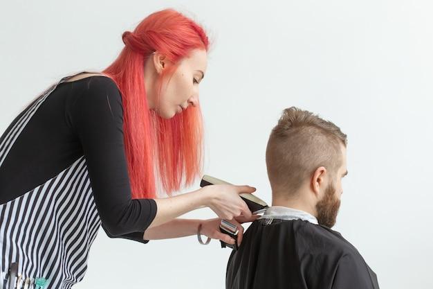 美容師、ヘアスタイリスト、理髪店のコンセプト-ひげを生やした男性をカットする女性のヘアスタイリスト