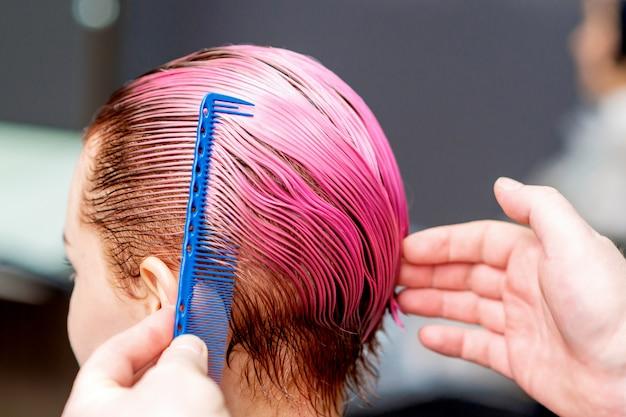 Hairdresser hand combs hair.