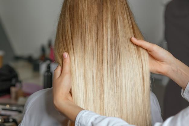 スタイリング後にクライアントのストレートヘアを持っている美容師の手