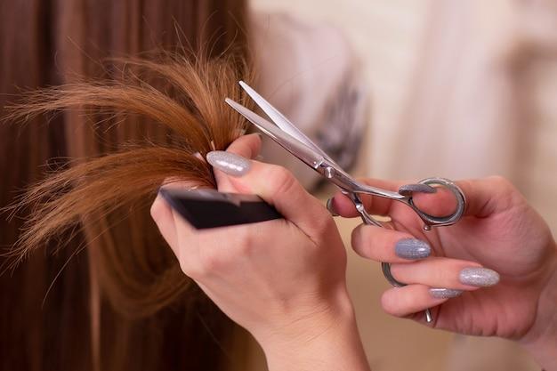 はさみとブルネットの髪を持っている美容師の手
