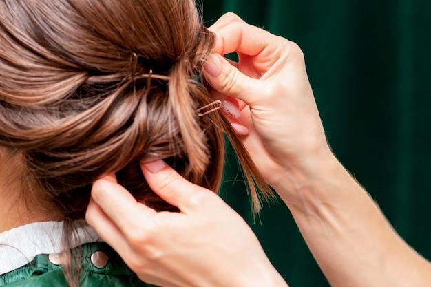 Руки парикмахера делают прическу на волосах женщины, крупным планом.