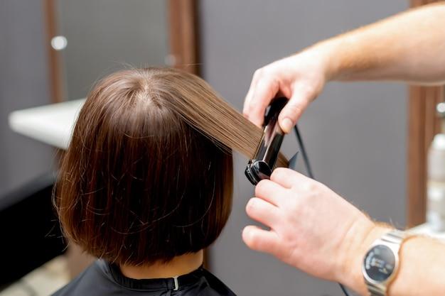 Руки парикмахера выпрямляют волосы женщины с выпрямителем в парикмахерской, вид сзади.