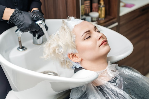Hairdresser hands are washing a woman's hair in a sink after hair coloring.