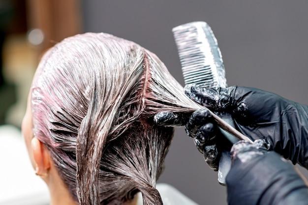 Парикмахер руки красят волосы женщины в черных перчатках, крупным планом.