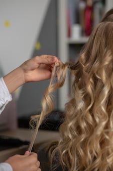 美容院でスタイリング中に流行のクライアントのカールを保持している美容師の手。クローズアップショット