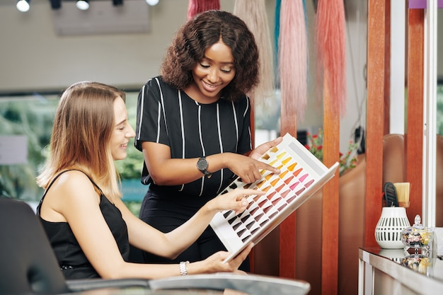 Hairdresser helping client to choose new hair color