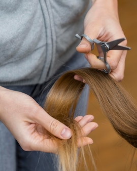 Hairdresser holding lock of hair and scissors