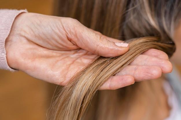 Hairdresser holding tuft of hair