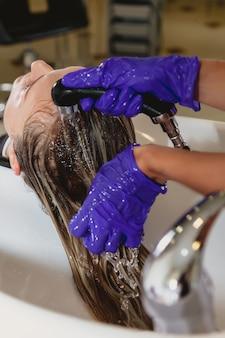 Парикмахер в салоне красоты моет голову клиента водой перед процедурой стрижки или окрашивания волос. услуги парикмахера спа и салон красоты. молодая женщина, мыть волосы. концепция укладки волос