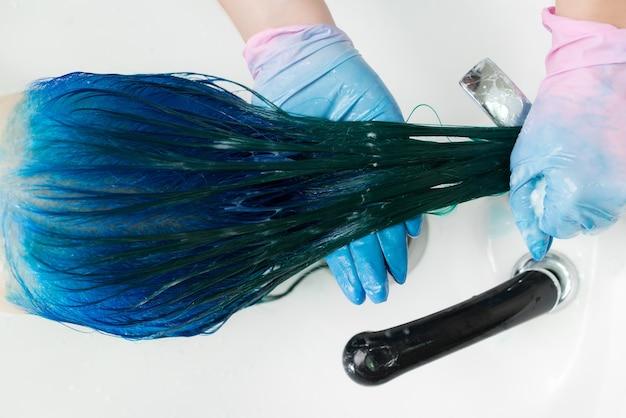 장갑을 낀 미용사는 머리 염색 과정 후 긴 머리 사파이어 색으로 고객의 머리를 씻는다
