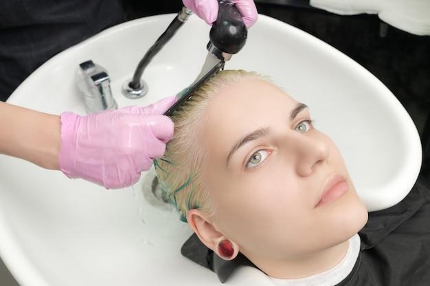 보호장갑을 끼고 고객의 녹색 머리를 빗질하는 미용사, 특수 세면대에서 샤워실에서 머리를 씻는 동안
