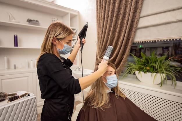 ヘアドライヤーでクライアントのブロンドの髪を乾燥させる保護マスクの美容師