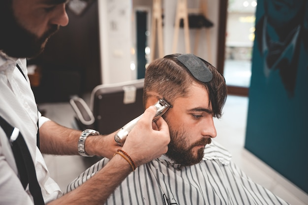 Hairdresser is carefully focused on the client's haircut.