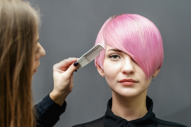 Hairdresser is combing short pink hairstyle.