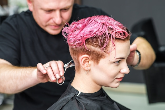 Hairdresser is cutting pink hair of a female.