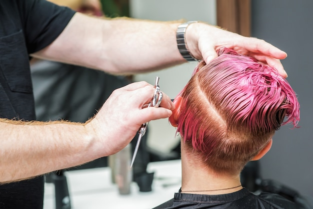 美容師は、若い女性のためにピンクの髪をカットしています。