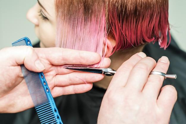 Hairdresser is cutting pink hair.