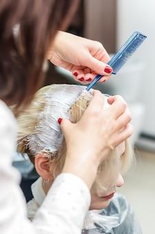Парикмахер красит волосы женщины белой краской
