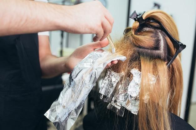 Парикмахер красит женские волосы, делая мелирование своей клиентке фольгой. выборочный фокус.