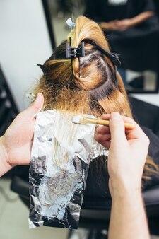 Парикмахер красит женские волосы, делая мелирование своей клиентке фольгой.