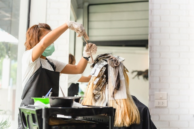 Hairdresser is dying female hair with foil