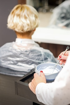 Парикмахер готовит белый краситель в контейнере на клиентке-женщине