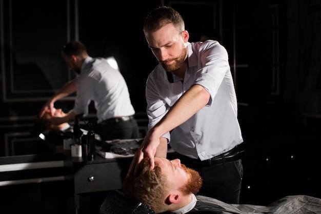 미용사는 칼로 남성 수염을 면도하고 있습니다. 잘 생긴 수염 난 남자는 이발소에서 미용사에 의해 면도되고있다
