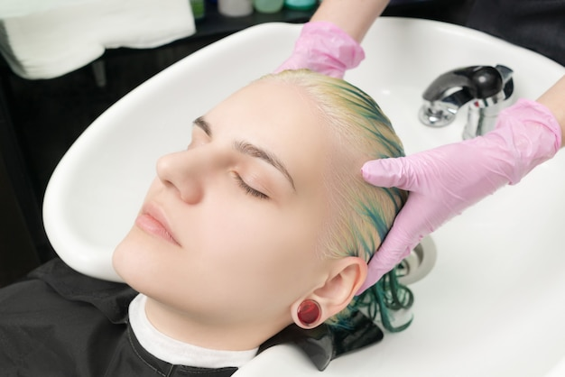Hairdresser lathers clients head with hair conditioner, washing head in special sink in beauty salon
