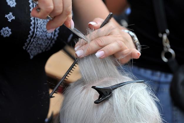 Парикмахер делает стрижку пожилой женщине.