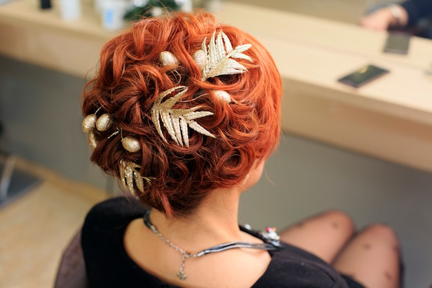 Hairdresser makes beautiful christmas hairstyle at the salon