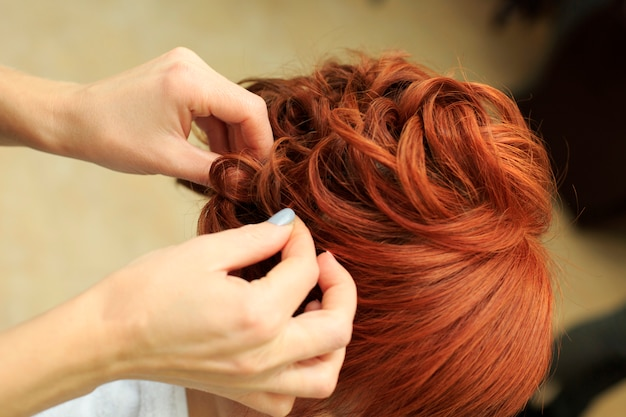 Hairdresser makes beautifull hairstyle at the salon c