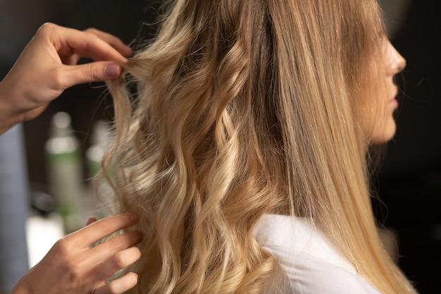 Парикмахер делает локоны на длинных светлых волосах красивой молодой женщине