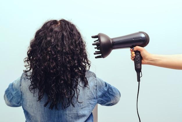 美容師は女性のための巻き毛のヘアスタイルを作ります。ヘアケアのコンセプト。特別なディフューザーノズルを備えたヘアドライヤーで巻き毛をスタイリングする女性。モダンなヘアドライヤーを使用している女の子。