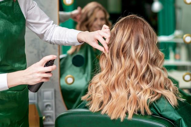 Парикмахер делает вьющиеся прически для женщины в салоне красоты, вид сзади.