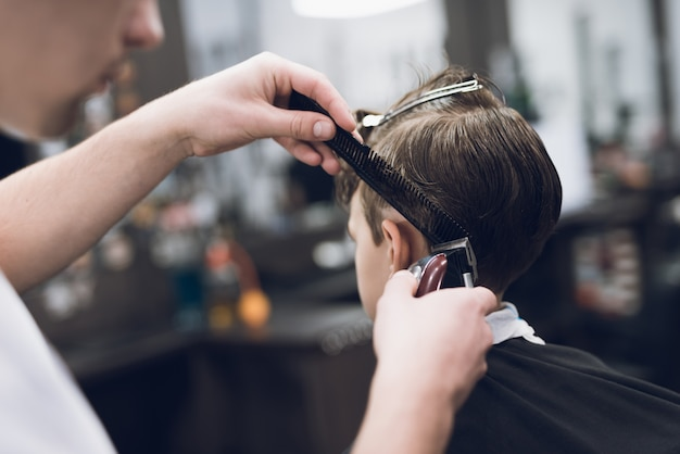 Hairdresser makes fashionable pretty hairstyle for the boy.