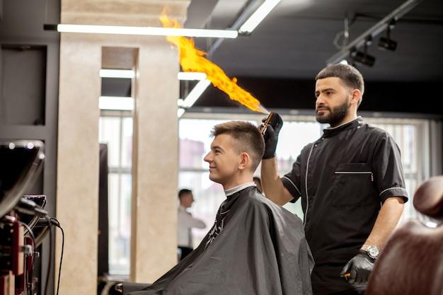 Парикмахер делает прическу мужчине. мастер-парикмахер делает прическу машинкой для стрижки волос