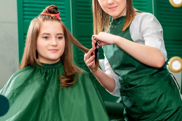 Hairdresser makes hairstyle for beautiful woman while looking in mirror reflection at beauty salon.