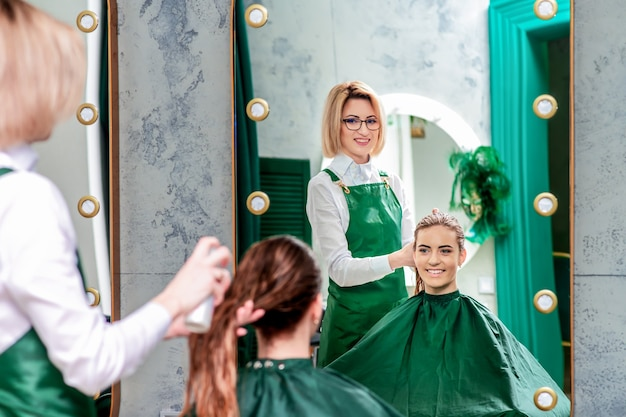 Hairdresser makes hairstyle for beautiful woman while in the mirror reflaction at the beauty salon.
